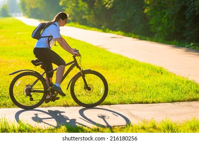 girl on bike rides on the bike path in the park