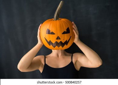 girl on a black background is holding a pumpkin with a painted face, instead of heads. Celebration concept Halloween