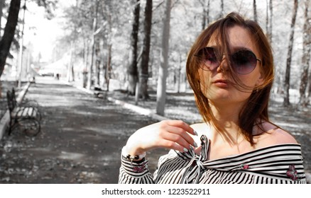 Girl on a black and white background in the park. Beautiful young model. Eyes closed from the pleasure of the wind. Warm season. The girl lengthened her shoulders. Solitude with nature.