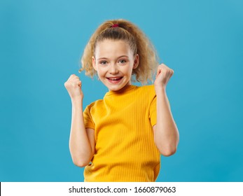 Girl on a blue background in a yellow T-shirt model