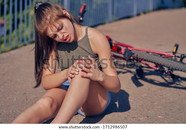 The girl on the bridge fell off the bike. Sits with his mouth open looking at a bruised knee.