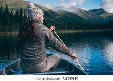 Girl on a canoe is in awe with the beautiful landscape at Juneau Lake, Alaska