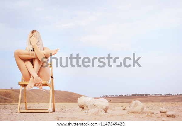 girl on the chair crossing her legs with her hands. The concept of meditation, healthy lifestyle. Training of spirit and body.