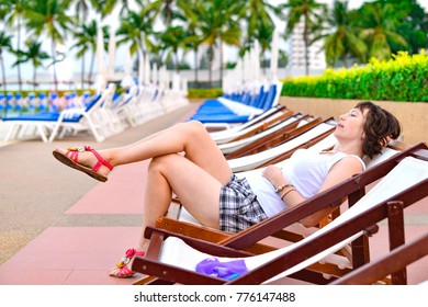 The girl on a chaise lounge is resting on the background of the palms in the hotel.