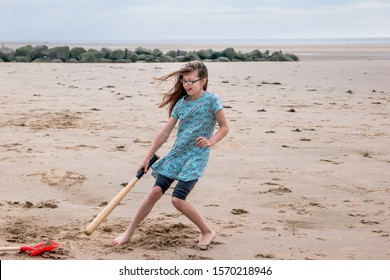Girl on a family seaside holiday playing cricket with a baseball bat on the beach