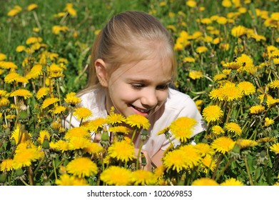 Girl on the field of yellow dandelions
