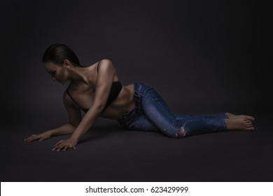 Girl on the floor in the studio on a gray background