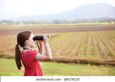 A girl is on the grass looking through her black binoculars towards the mountains and cane field.  A child being a spy.