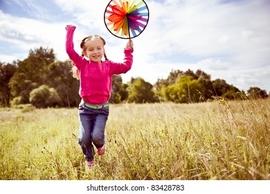 Girl on grass in summer  day holds windmill in hand