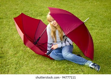 Girl on the grass with two umbrellas