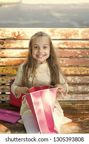Girl on happy face unpacking shopping bags or presents, bench on background. Girl surprised by unexpectable presents or gifts. Kid girl with long hair excited about presents. Surprise concept.