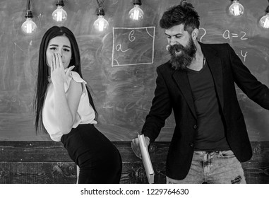 Girl on helpless face punished by teacher. Schoolmaster punishes sexy student with slapping on her buttocks with book. Man with beard slapping sexy student, chalkboard on background. Role game concept