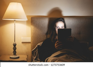 Girl on the internet by touch tablet before bed in bed. Woman surfing the web before sleep