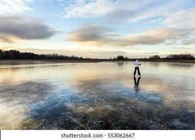 Girl on the lake ice, skate merrily.