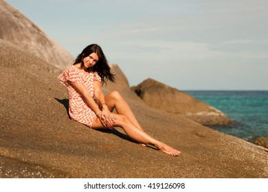 Girl is on the large stone on the beach