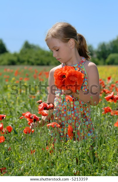 Girl on meadow with a bunch of poppies