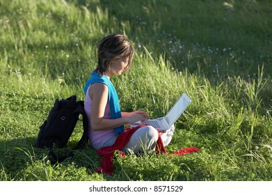 girl on a meadow relaxing and using a laptop