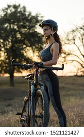 Girl on a mountain bike on offroad, beautiful portrait of a cyclist at sunset, Fitness girl rides a modern carbon fiber mountain bike in sportswear. The girl looks towards freedom and relaxation.