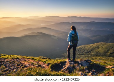 Girl on mountain peak with green grass looking at beautiful mountain valley in fog at sunset in summer. Landscape with sporty young woman, foggy hills, forest, sky. Travel and tourism. Hiking