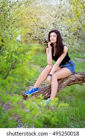 a girl on nature sits on a log