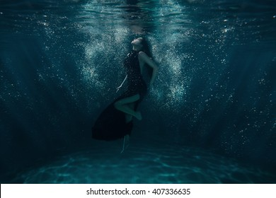 Girl on the ocean floor among the light beams passing through water.
