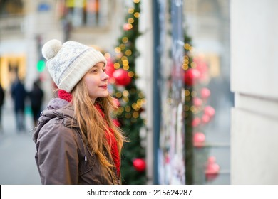 Girl on a Parisian street looking at shop windows decorated for Christmas