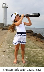 Girl on pier at sea looks through spyglass