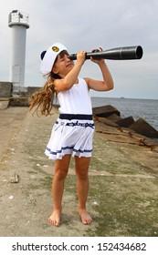 Girl on pier at sea looks through spyglass