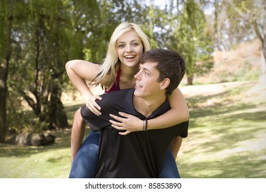 Girl on piggyback of boy friend in green park with trees