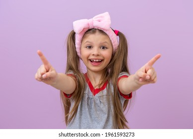 A girl on a purple isolated background points her fingers in different directions.