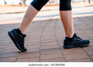 girl on race walking. legs in black sweatpants and black sneakers. side view