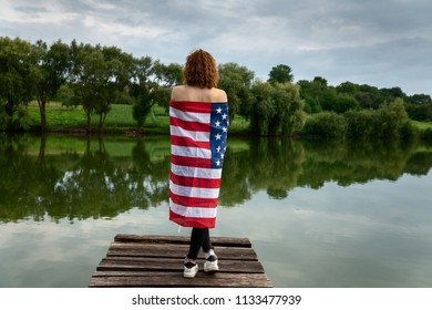 0120fce110a Girl on the river bank with the US flag. The wound in the flag is