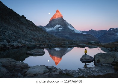 A girl on a rock in the Riffelsee watching the first sunlight on the Matterhorn.
