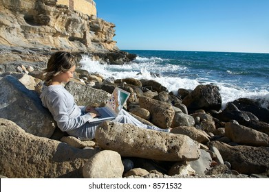 girl on the rocks near the sea relaxing and using a laptop