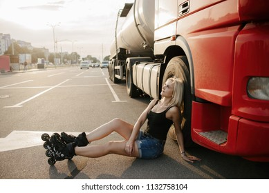 A girl on roller skates sitting near a red truck