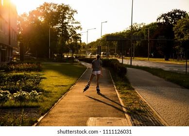 girl on roller skates, sunset in the city