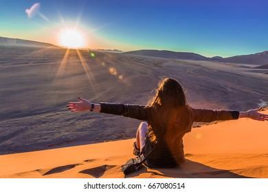 Girl on sand dune in desert during sunrise. Real Lens Flare Effect