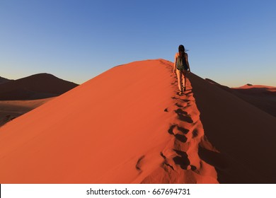 Girl on sand dune in desert during sunrise.  Sossusvlei, Namib Naukluft National Park, Namibia. Concept of wanderlust in namibian famous desert .