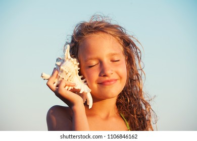 Girl on sea background. Child put the shell to her ear. Summer vacation.