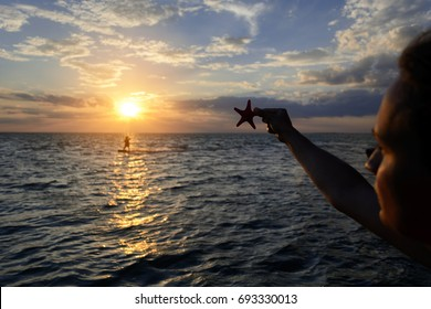 Girl on the seashore is holding a starfish. Silhouetted photo in the sun lights