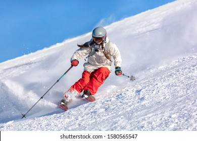 Girl On the Ski. a skier in a bright suit and outfit with long pigtails on her head rides on the track with swirls of fresh snow. Active winter holidays, skiing downhill in sunny day. Dynamic picture