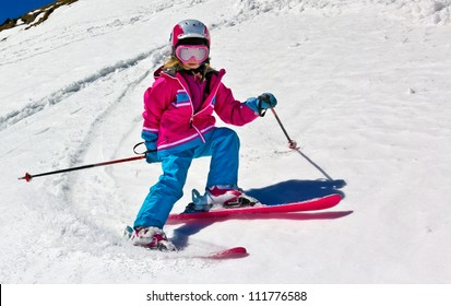 Girl on skis in soft snow on a sunny day in the mountains, on a steep slope.