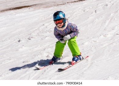 Girl on skis in soft snow on a sunny day in the mountains