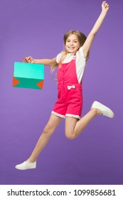 Girl on smiling face carries shopping bag and jumps, isolated on white background. Girl likes to buy fashionable clothes in shopping mall. Kid girl with long hair fond of shopping. Shopping concept.