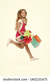 Girl on smiling face carries bunches of shopping bags, isolated on white background. Kid girl with long hair fond of shopping. Shopping concept. Girl likes to buy fashionable clothes in shopping mall.