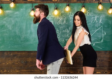 Girl on smiling face having fun while punishes teacher. Student lady slapping on teachers buttocks with book. Role games concept. Man with beard punished by sexy student, chalkboard on background.