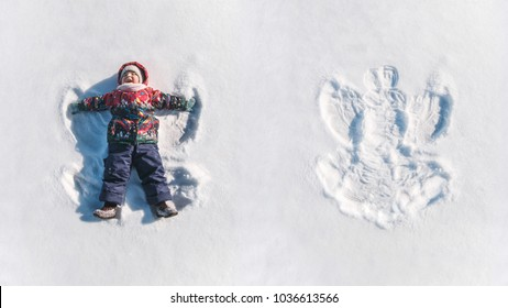The girl on a snow angel shows. View from top. Cute beautiful young happy kid making snow angel while lying on snow. Child of two years old. Baby smile.