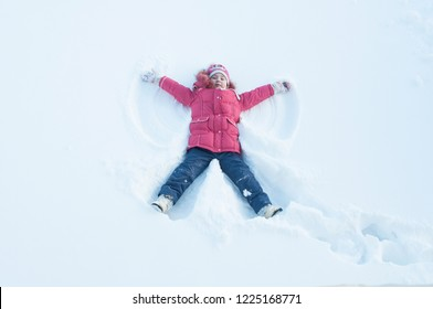 The girl on a snow angel shows. snow angel. Top View Flat Lay
