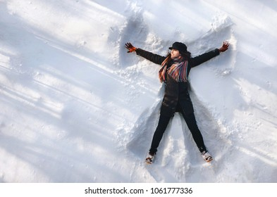 A girl on the snow shows an angel. Spreading arms. Top view. Drone. Smile. Happy.