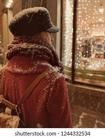 The girl on a snowy street at the window